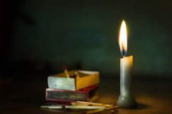 stand in dark candle lit with match box and sticks lying on floo Royalty Free Stock Image