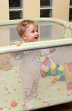 Stand de bébé dans le playpen photographie stock libre de droits
