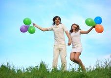 Stand de couples dans l'herbe avec des ballons Image libre de droits