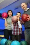 Stand de famille bord à bord et billes de prise pour le bowling Photographie stock libre de droits
