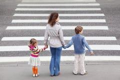 Stand de famille près de route en travers, derrière Photo stock