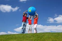 Stand de famille sur l'herbe et le globe de levage Photo libre de droits