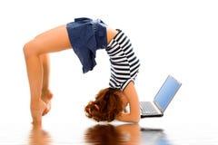Stand de fille de beauté sur la tête avec l'ordinateur portatif photo libre de droits