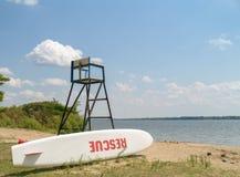 Stand de maître nageur avec la planche de surfing de sauvetage Photographie stock
