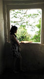 Stand der jungen Frau am dunklen Fenster Stockfotografie