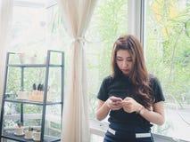 Stand der jungen Frau, der Telefon spielt Lizenzfreie Stockfotografie