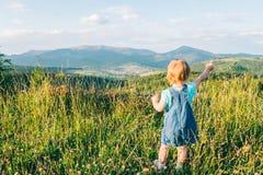 Stand des kleinen Mädchens auf der Spitze und Schauen auf Bergen Stockfotografie