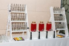 Stand with empty beakers for drinks. Glasses glasses for juice or cocktail on shelf in restaurant Stock Image