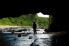 Stand at the entrance of cave near by the sea Royalty Free Stock Photo