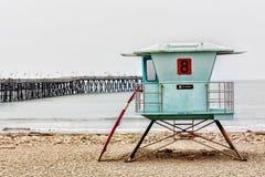 Stand et planche de surfing de maître nageur au pilier de Ventura Photos stock