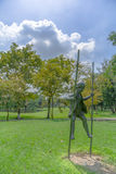 Stand Firmly. Bronze statue of a kid standing on standing sticks on a grass while the sun shines brightly from behind Stock Photo