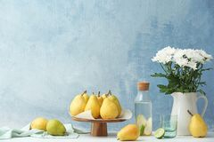 Stand with fresh ripe pears on table. Against color background royalty free stock photography