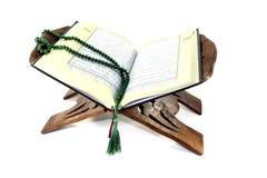 Stand mit einem geöffneten Quran und einem Rosenbeet Stockfotos