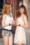 Stand mit zwei sprechen der nette Mädchen und miteinander Stockfotografie
