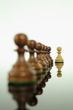Stand out. Light colored wooden chess pawn standing out from the rest Stock Photo