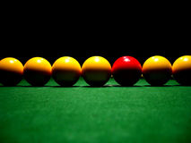 Stand out from the crowd 1. A line of pool balls on a table, one red royalty free stock photography