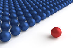 Stand Out From the Crowd. Computer generated blue and red spheres on white background Stock Photos