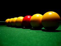 Stand out from the crowd 2. A line of pool balls on a table, on red stock photo