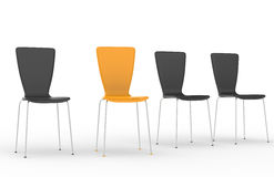 Stand out from the Crowd. Chairs in a row, 3 Black and one Orange Stock Image