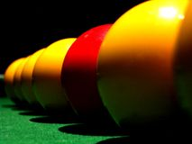 Stand out from the crowd 3. A line of pool balls, one red royalty free stock image