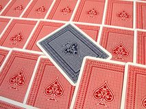 Stand out from the crowd. A blue playing card, face down, on background of red cards Royalty Free Stock Photo