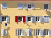 Stand out from the crowd. Being different concept, Red shutter among grey shutters Stock Photography
