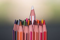 Stand out from the Crowd. Color pencils macro. Stand out from the Crowd macro concept with colored pencils. White pencil standing higher from the rest of the stock photos