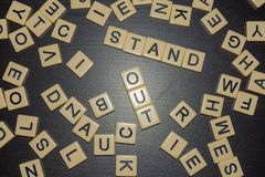 Stand out in the crowd letter tiles lined up in a mix of tiles on a black background. Conceptual. Be different. royalty free stock photography
