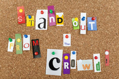 STAND OUT FROM CROWD. STAND OUT FROM the CROWD single letters pinned on cork noticeboard Stock Photo