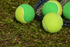 Stand out from the crowd. A tennis ball, solid, poses with several balls used in children's tennis training, which are of two colors. The background of the photo royalty free stock photo