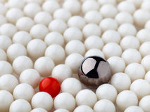 Stand out red and metal balls surrounded by white balls. Selective focus Royalty Free Stock Photos
