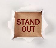 Stand out. 'Stand out' text printed on brown paper with white tear paper Royalty Free Stock Photography