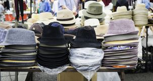 Stand of a street market with hats and bonnets for sale stock image