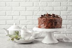 Stand with tasty homemade chocolate cake and tea set. On table stock images
