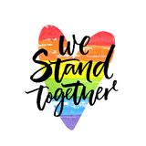 We stand together. Inspirational LGBT slogan han dwritten on rainbow flag heart. We stand together. Inspirational LGBT slogan han dwritten on rainbow flag heart Stock Photo