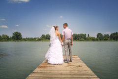 Stand together. Young happy newlyweds walking and posing on a riverside Royalty Free Stock Photography