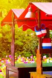 Stand with traditional Holland symbols in national colors taken against sunset light. Blurred colorful tulips in the background. Traditional Dutch wooden clogs stock photo