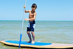 Stand Up. Boy holding Stand Up paddle board Royalty Free Stock Photo