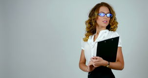 Stand-up footage of a young cheerful business woman with black paper holder in her hands. stock video