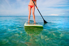 Stand up paddle board. Woman on stand up paddle board in turquoise water with red bikini Stock Images