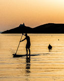 Stand up paddle board man. A man stand up paddle boards during sunset in the Greek island of Kea Stock Images