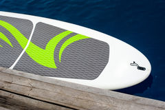 Stand up paddle board SUP. Empty board at a wooden pier without people royalty free stock image