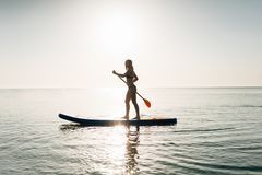 Stand up paddle board woman paddleboarding on Hawaii standing happy on paddleboard on blue water. Stand up paddle board woman paddleboarding on Hawaii . Young stock photos