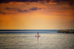 Free Stand Up Paddle Board Woman Silhouette On Water, Cagliari, Italy. Natural Background With Mediterranean Sea At Sunrise, The Sun Stock Photo - 158771430