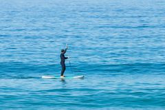 Free Stand Up Paddle Boarder In Wetsuit Paddling On A Sea. Minimalist Image Royalty Free Stock Photos - 152457568