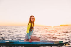 Stand up paddle boarding on ocean with warm sunset colors. Young girl relaxing on sea Royalty Free Stock Image
