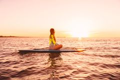 Stand up paddle boarding on a quiet sea with sunset colors. Woman on sup board Stock Photos