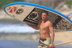 Stand Up Paddle surfer. Stand Up Paddle surfing or SUP, is a new sport that is growing rapidly. Atilla Jobaggyi carries his board and paddle to the surf Royalty Free Stock Photos