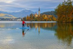 Stand Up Paddle Surfer at Bled Lake. With island and mountains reflected in the water on background at autumn day Stock Photo