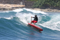 Stand Up Paddle surfing. Or SUP, is a new sport that is growing rapidly. Nelz Vellocido performs a difficult cutback at Makaha, Hawaii Stock Images